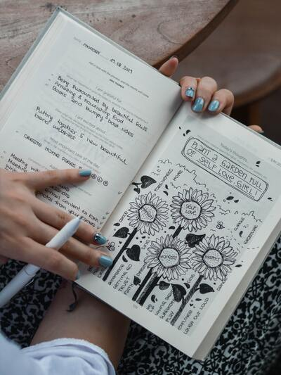 Pair of hands holding an open journal with visible doodles.